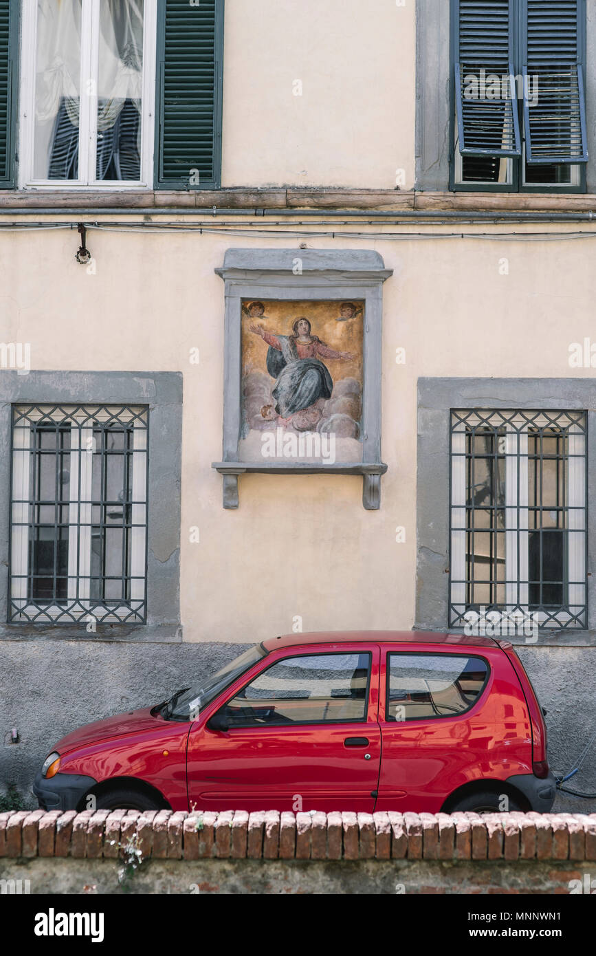 hight resolution of a tiny red car in front of an old building in lucca italy
