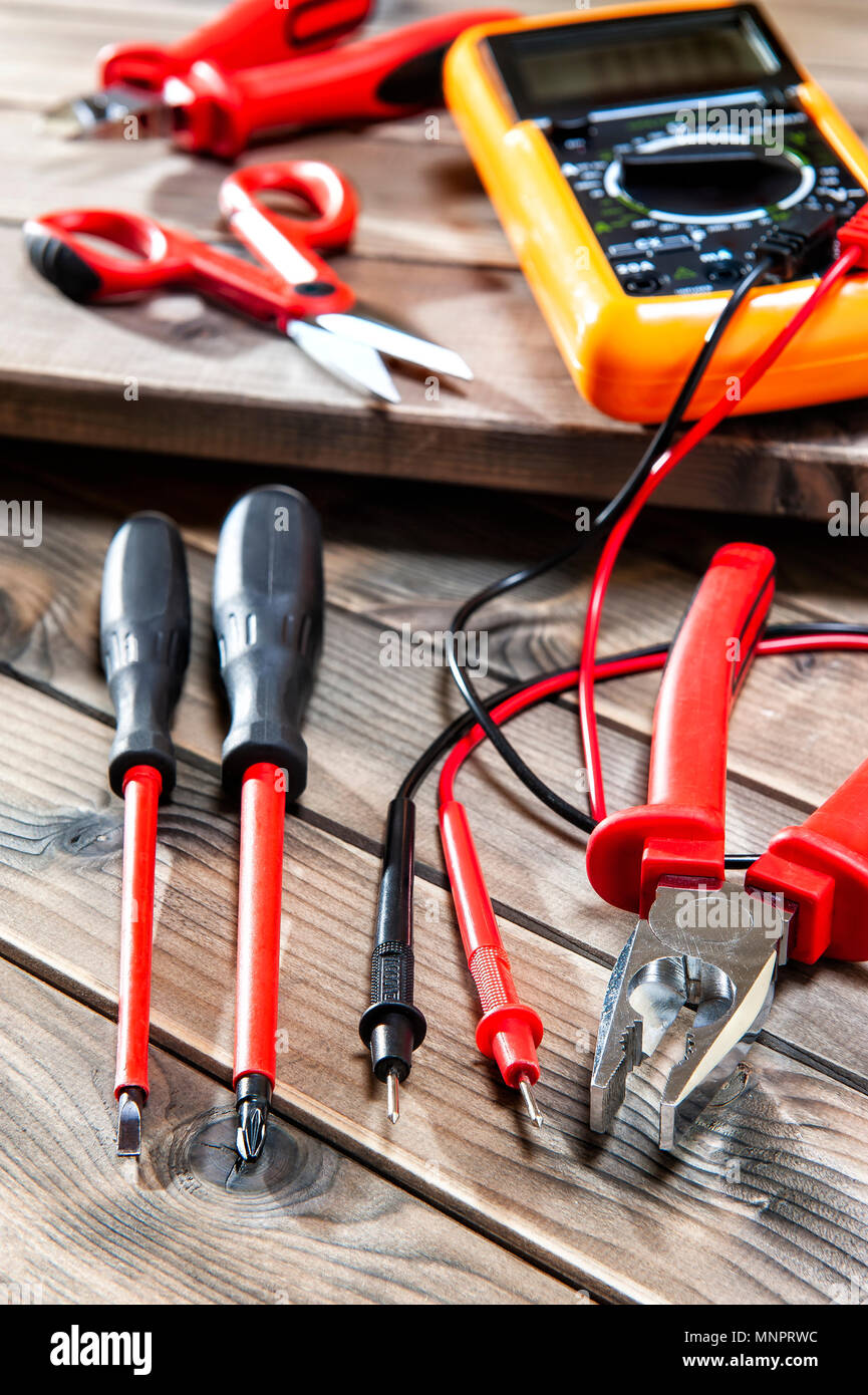 hight resolution of multimeter clamp cable cutter scissors and screwdrivers for working on a residential electrical system photographed on an antique wooden desk