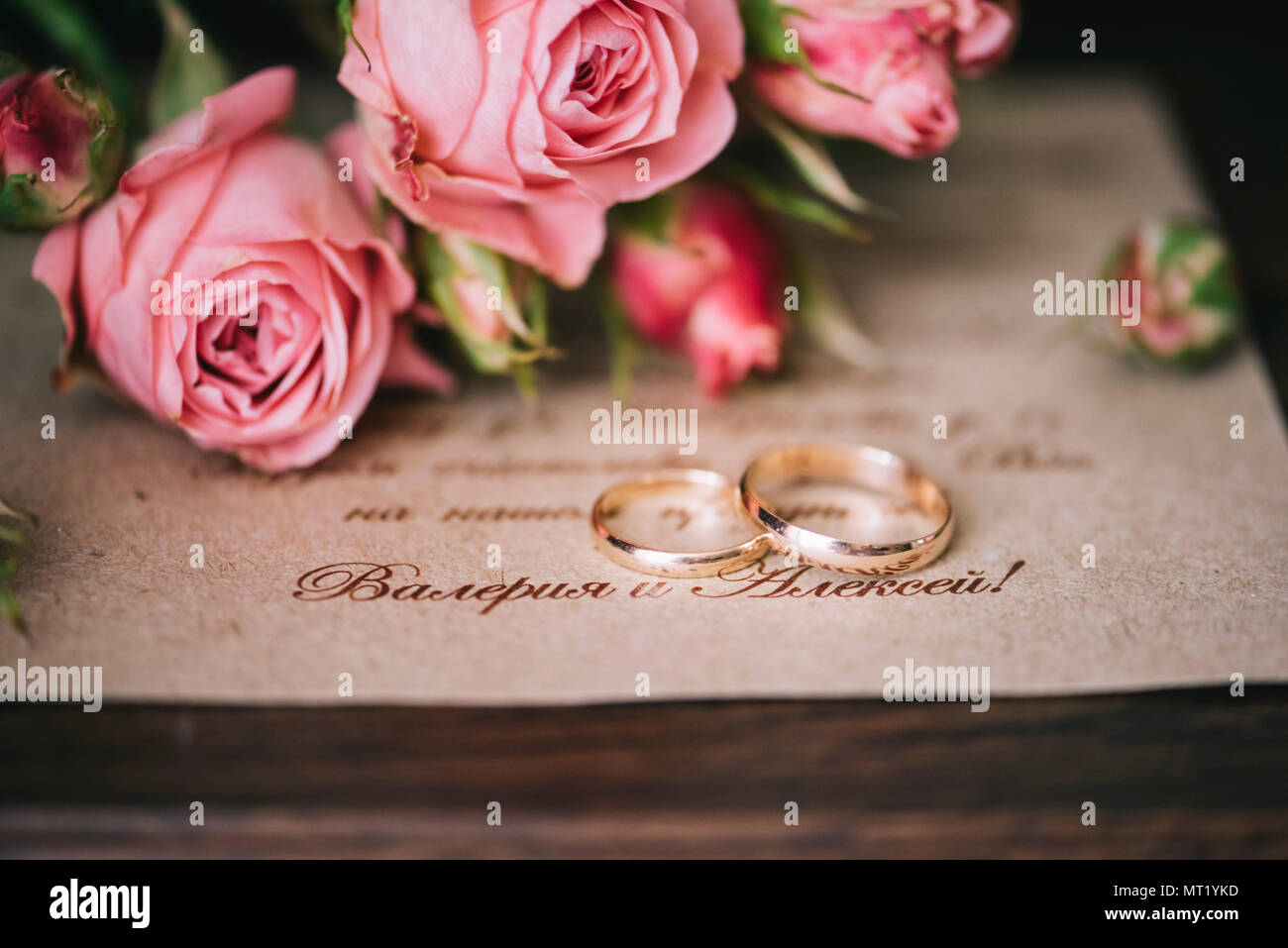 https www alamy com a pair of golden wedding rings on the wedding invitation card with some pink roses on the background image186899089 html