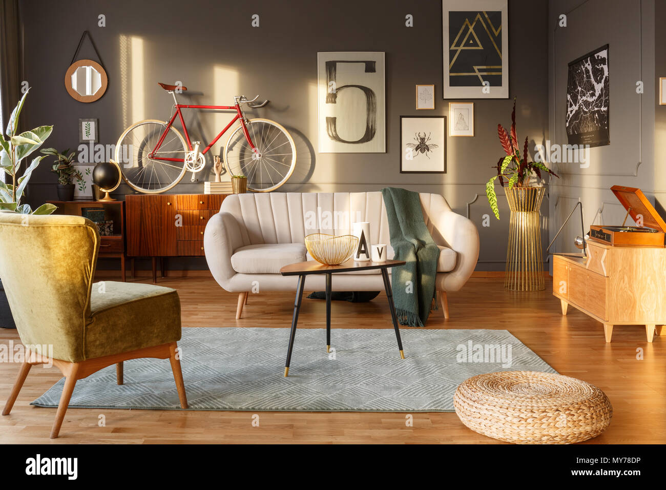 living room with light green carpet teal ideas color sofa vintage armchair sideboards gramophone and red bicycle against dark wall posters in a interior