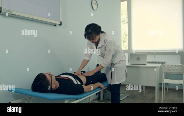 Female Doctor Doing Abdominal Examination On Male Patient