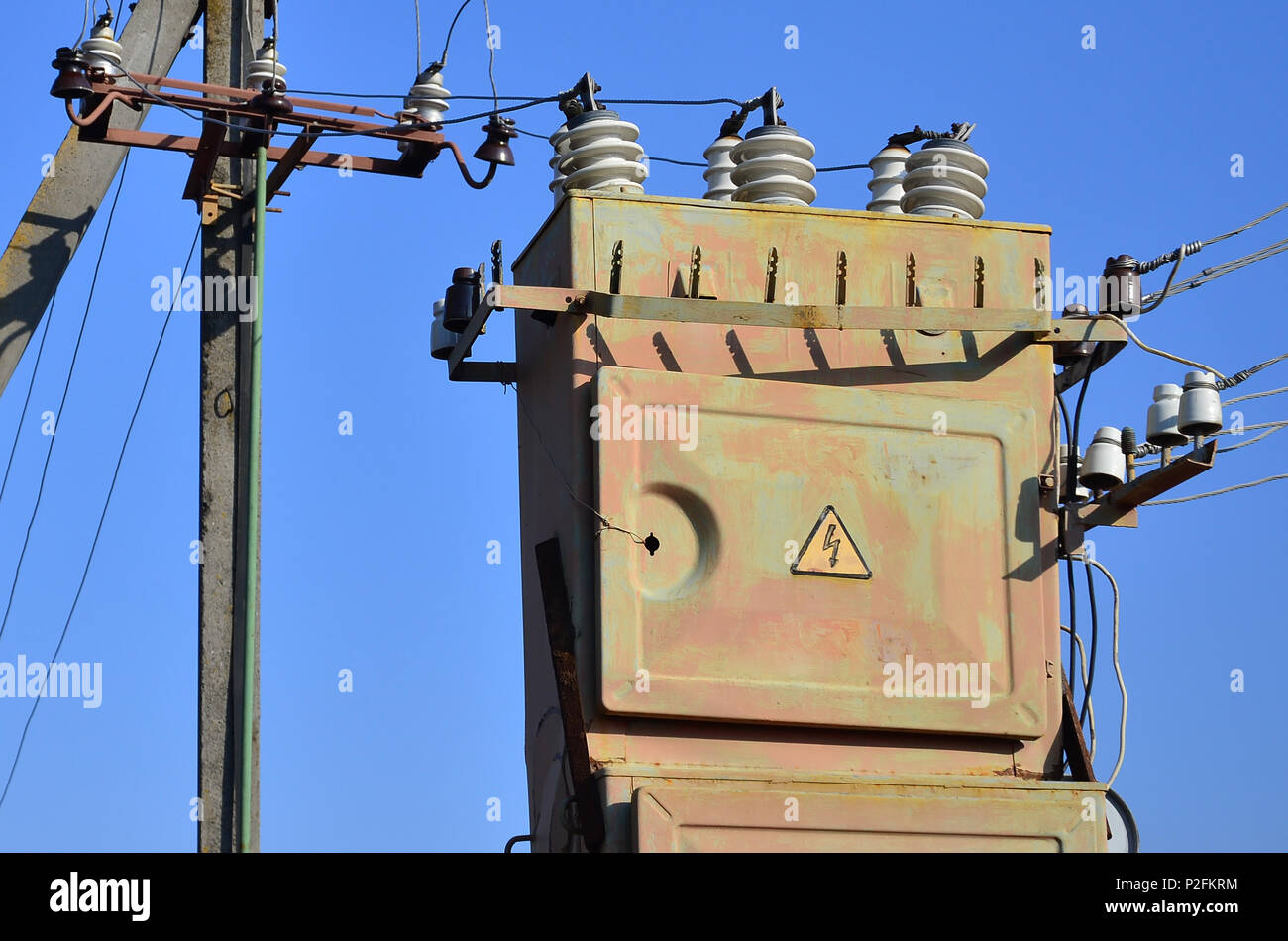 hight resolution of old and obsolete electrical transformer against the background of a cloudless blue sky device for distribution of supply of high voltage energy