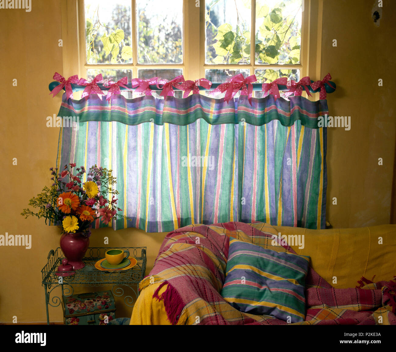cafe curtains for living room side table decorating ideas colourful striped tied with pink bows onto a brass rod on window in economy style cottage