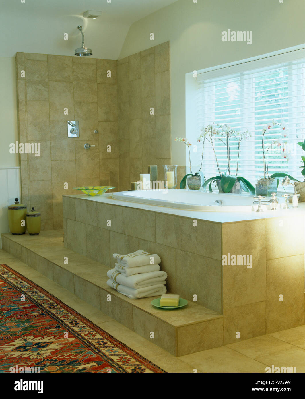 https www alamy com pile of white towels on step below travertine tiled bath in modern bathroom with wet room style shower image208941765 html