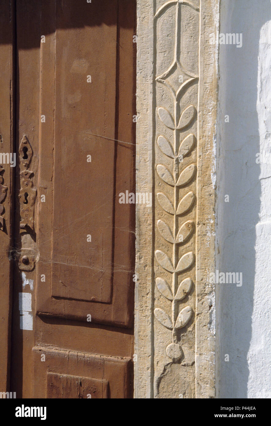 Ornate Stone Frame Around Brown Wooden Double Doors On Portuguese