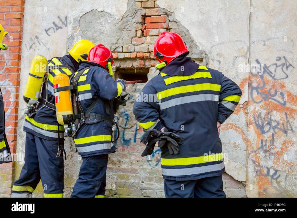 medium resolution of view from behind on firefighter in uniform with full safety gear using crowbar to break