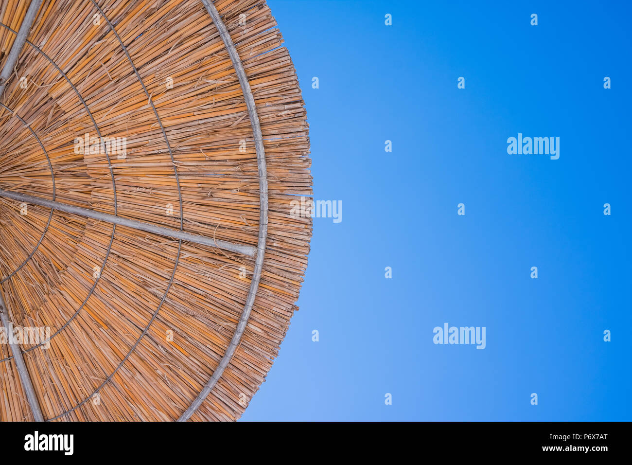 Straw Roof Of Sun Umbrella Against The Blue Sky Vacation Topic Summer Beach Background For An Inscription Texture Of Beautiful Straw Natural Sun Umbrellas Made From Hay In A Tropical Desert Resort Stock Photo