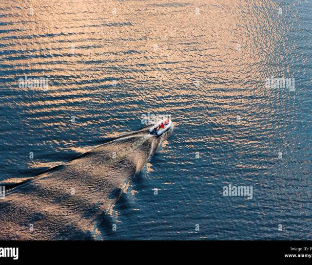 Aerial View Of A Small Boat On Wide Blue Water Surface In Evening Sun Diagonal Composition Suitable Background