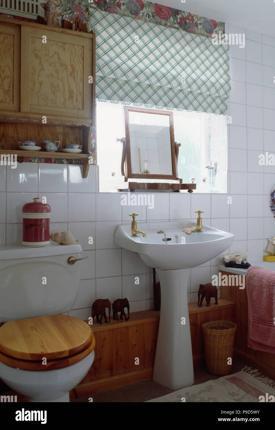 Wooden Cabinet Above Toilet With Wooden Seat In Small Bathroom With Green Checked Blind Above Pedestal Basin Stock Photo Alamy