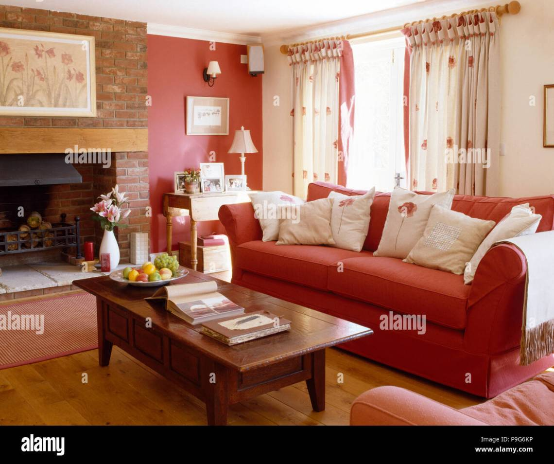 Wooden Coffee Table And Red Sofa With White Cushions In A Country Living Room With One Red Wall Stock Photo Alamy