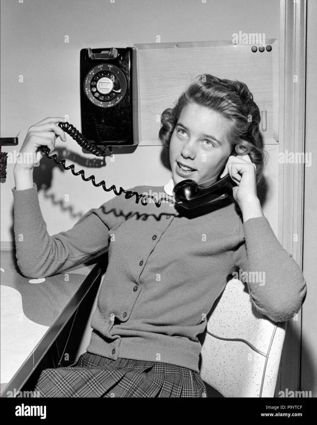 1950s teenage girl talking on wall mounted dial telephone