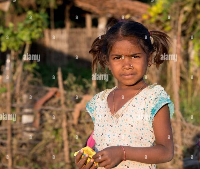 A Local Indian Girl Stands Outside Her House To See Tourists Walking By In Kanha Village