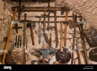 Wallpaper background of ancient medieval weapons hanged on a vintage stone and concrete wall History of war Stock Photo Alamy