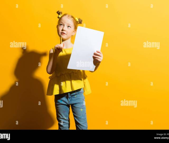 Girl With Red Hair On A Yellow Background A Beautiful Girl Is Holding A Pencil And A White Sheet In Her Hands The Child Pondered