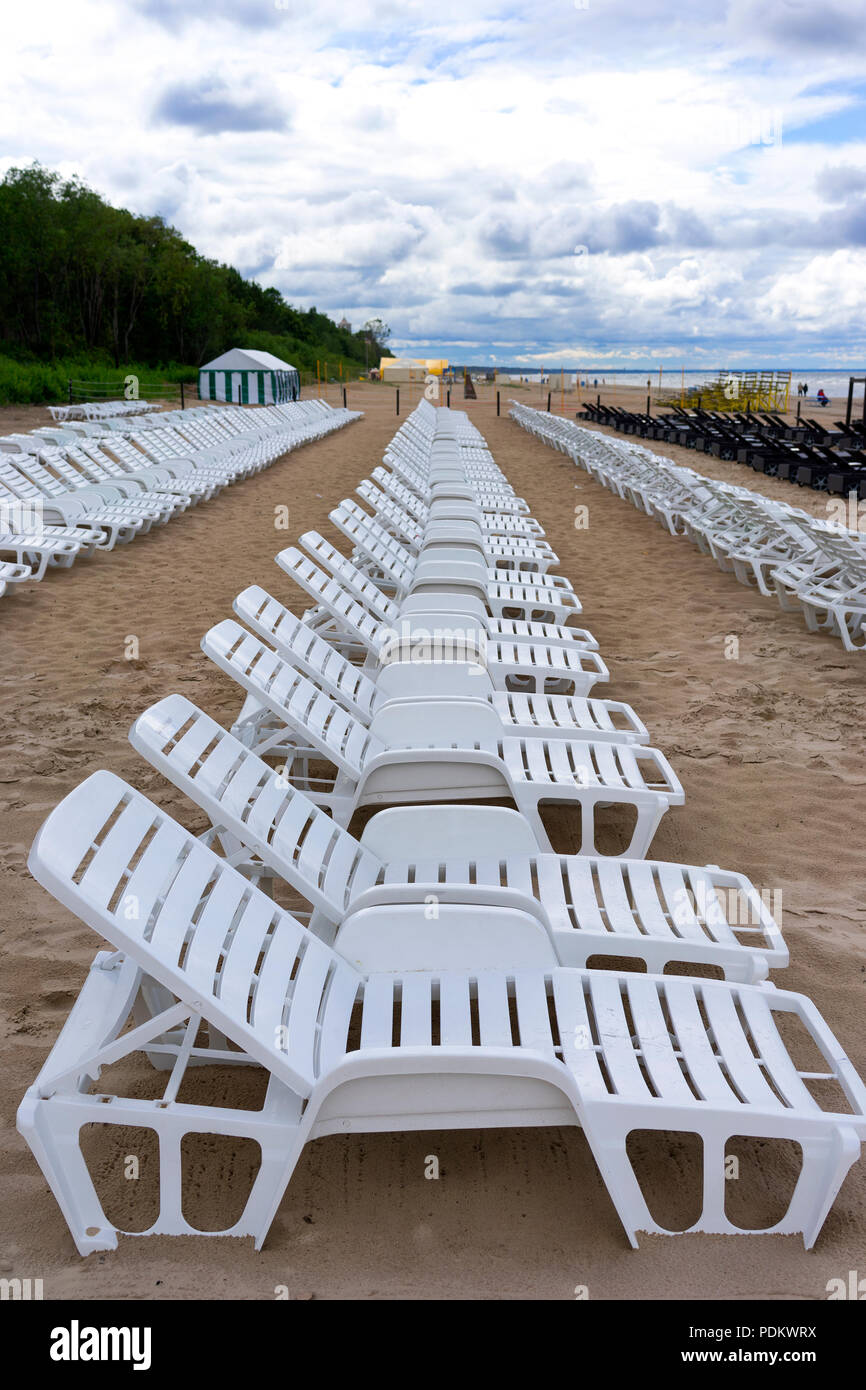 Sunbathing Chairs Row Of White Chairs For Sunbathing On The Sandy Beach After Rain
