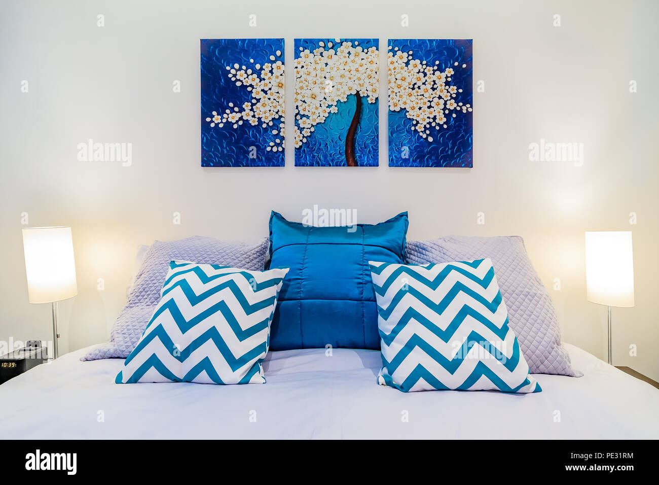 https www alamy com large bed with linnens and bright blue pillows in a modern bedroom wall art painting and lights image215196904 html