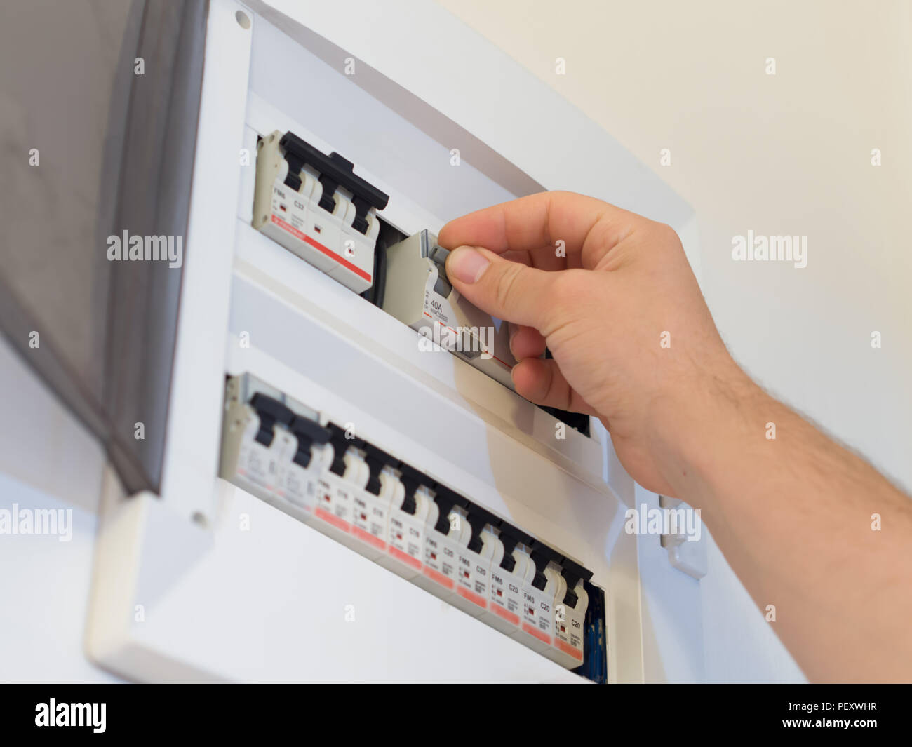 hight resolution of electricity fuse panel and lifting the fuse with hand stock image