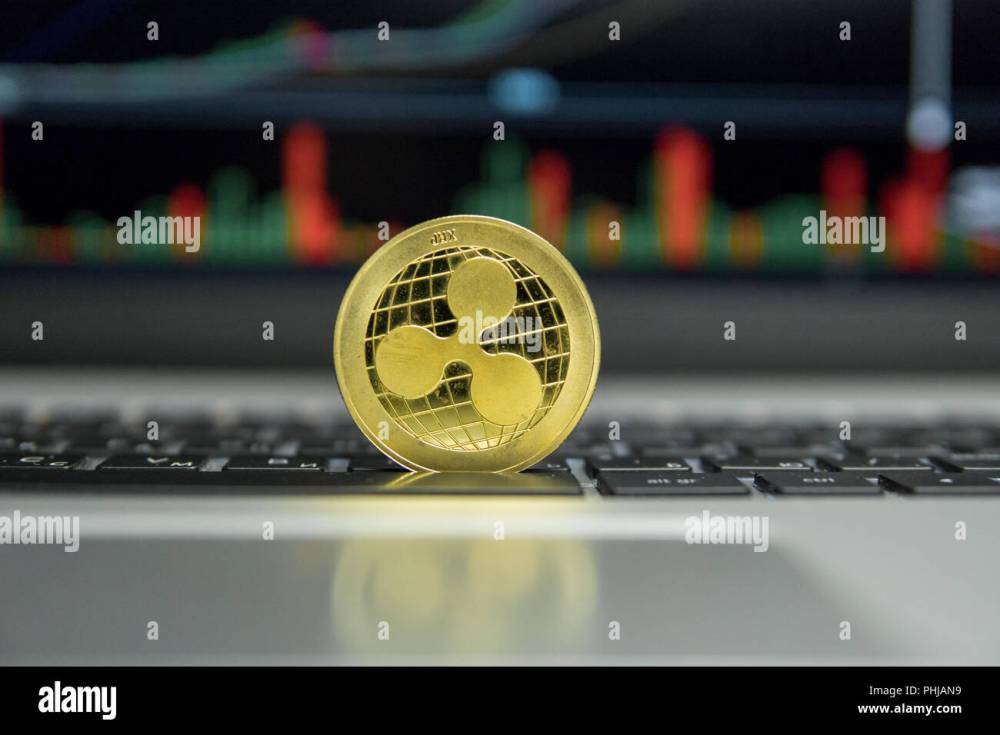 medium resolution of golden ripple coin on a black keyboard of silver laptop and diagram chart graph on a screen as a background virtual cryptocurrency concept