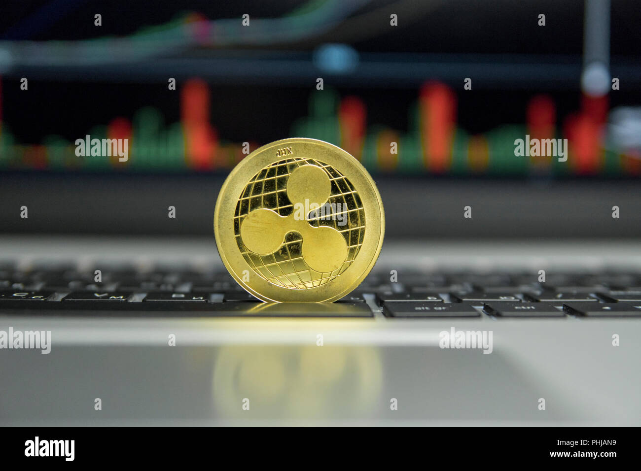 hight resolution of golden ripple coin on a black keyboard of silver laptop and diagram chart graph on a screen as a background virtual cryptocurrency concept