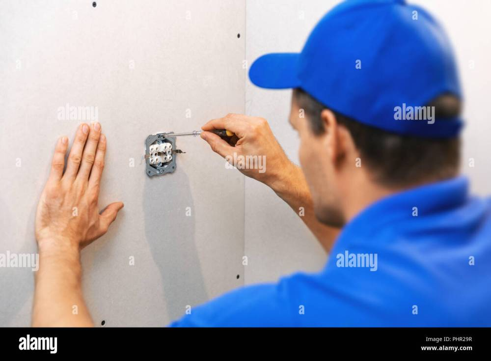 medium resolution of electrician installing electrical outlet on the wall stock image
