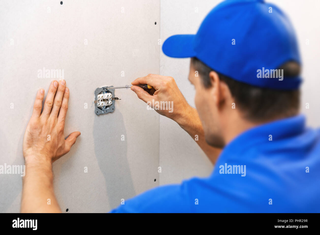 hight resolution of electrician installing electrical outlet on the wall stock image