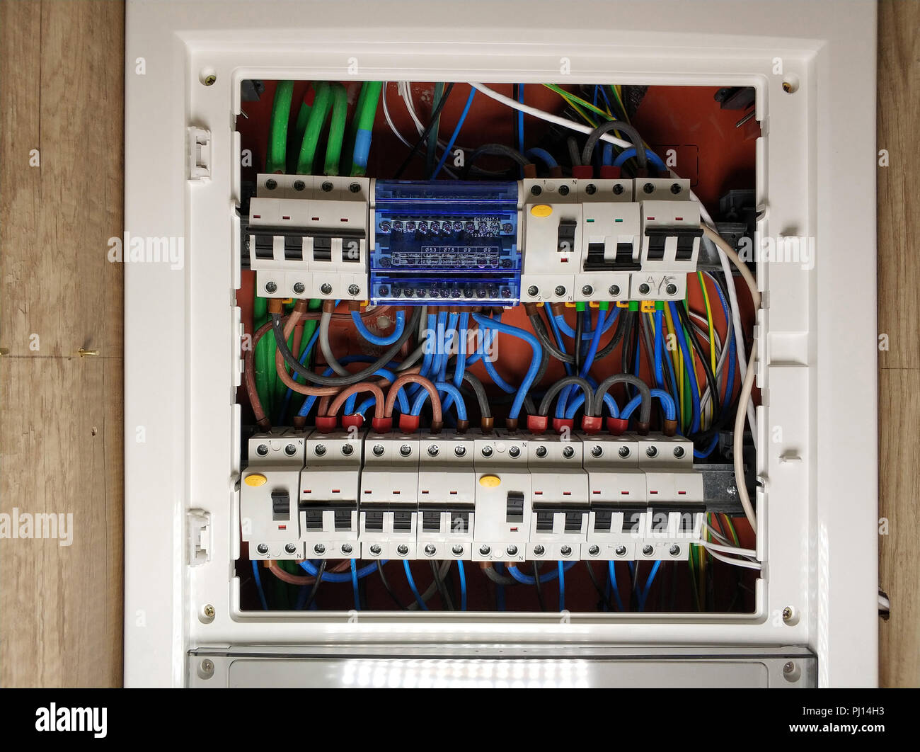 hight resolution of close up of white frame panel electrical switch board with colourful cables automatic circuit switchers breakers and fuses