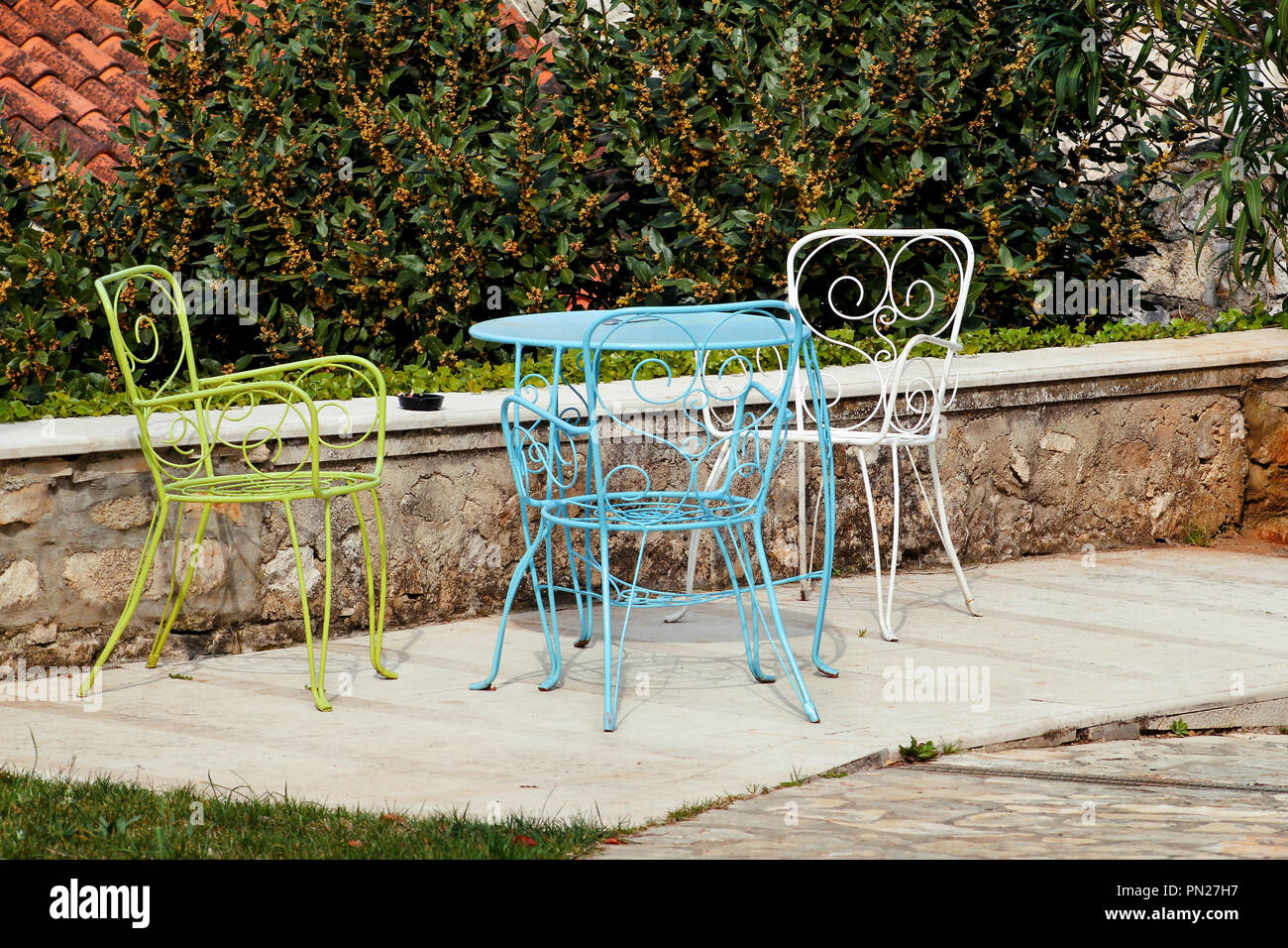 https www alamy com chairs and a table in garden colorful steel chairs and a table standing in a beautiful garden at sunny day patio furniture a set of three colored image219482067 html
