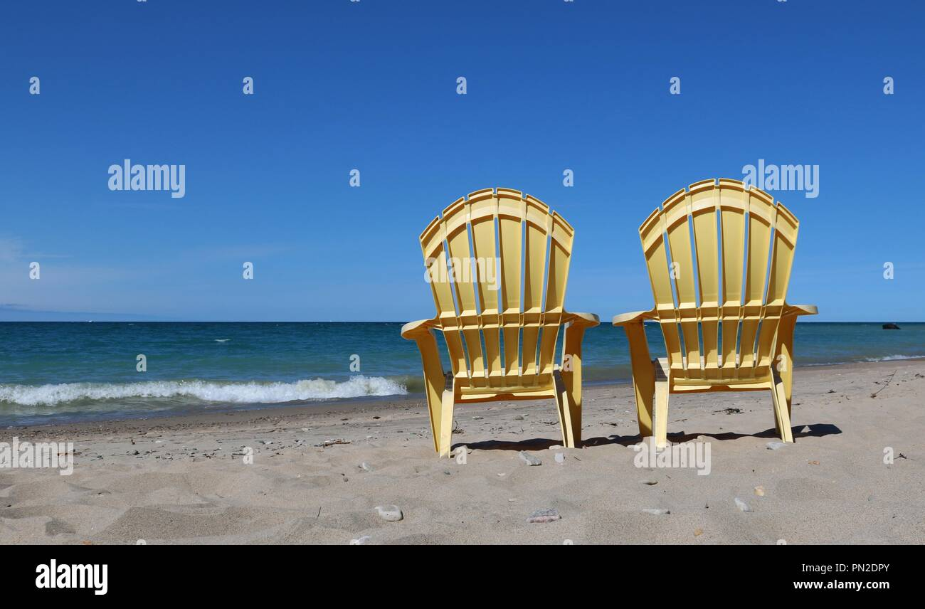 folding lawn chairs ontario modern tables and plastic stock photos images two yellow on the edge of lake huron a