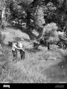 1930s Two Boys Fishing With Stick And String Rods