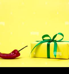 red sharp useful bitter delicious vegetable pepper bright yellow gift box on a simple background symbol of love power and passion [ 1300 x 956 Pixel ]