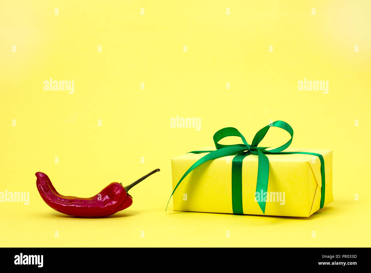 hight resolution of red sharp useful bitter delicious vegetable pepper bright yellow gift box on a simple background symbol of love power and passion