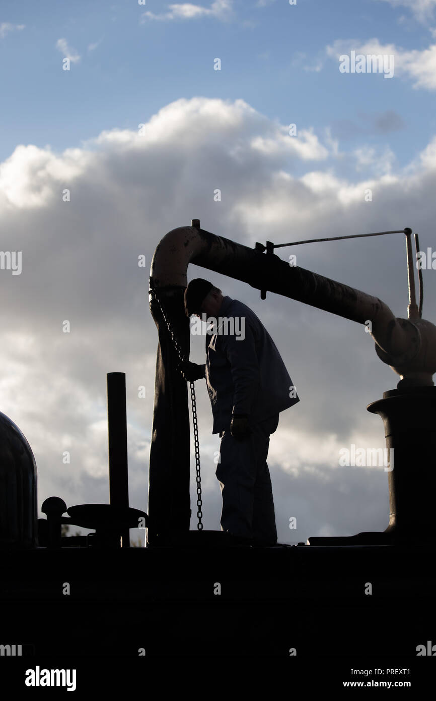 hight resolution of close up of steam train driver in silhouette against sky stood on vintage locomotive