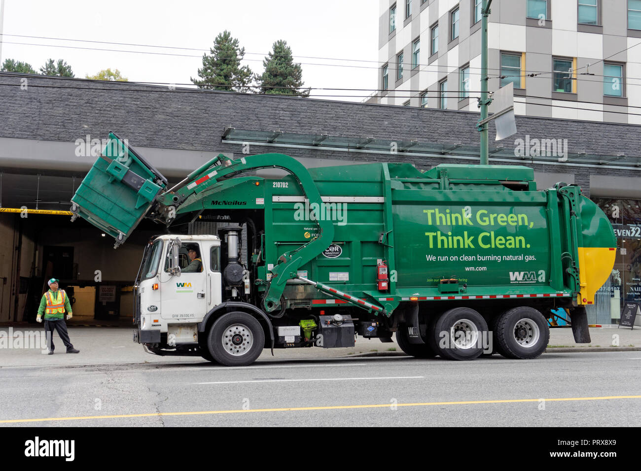 hight resolution of green clean energy waste management garbage truck lifting a dumpster vancouver bc canada
