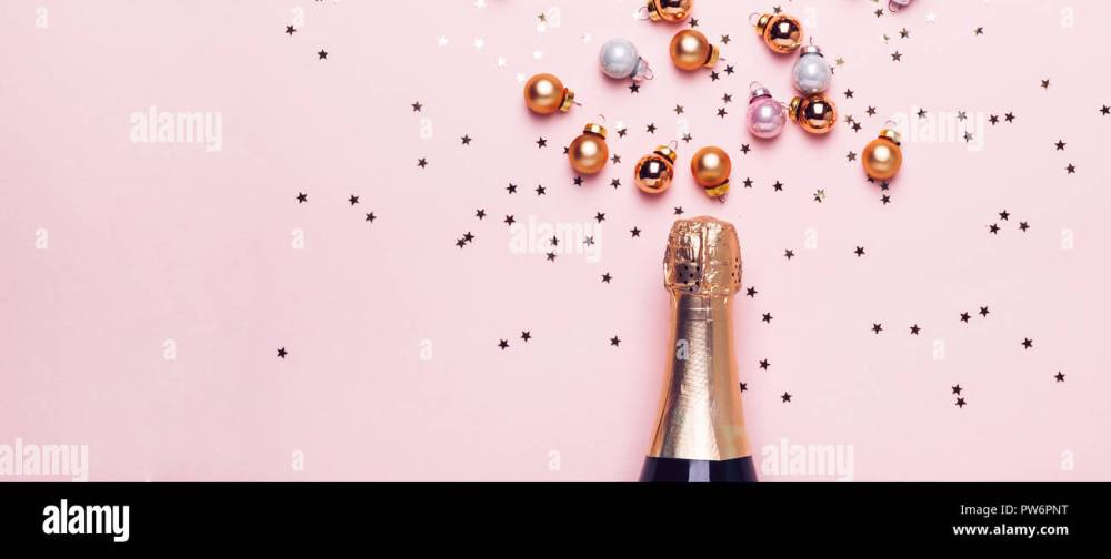 medium resolution of champagne bottle and scattering of golden shiny balls and confetti on pink background banner format