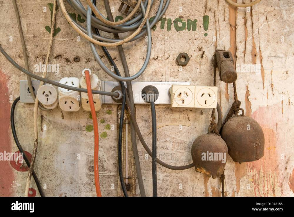 medium resolution of an australian electrical power board with multiple plugs and leads attached and hanging on a wall