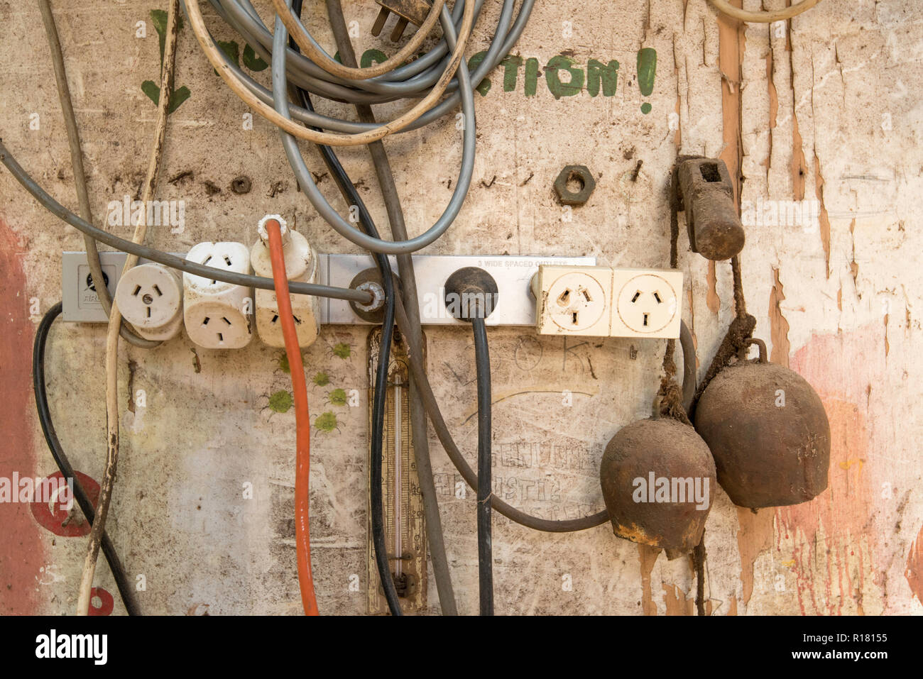 hight resolution of an australian electrical power board with multiple plugs and leads attached and hanging on a wall