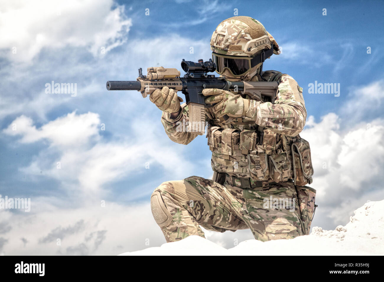 hight resolution of fully equipped with tactical ammunition airsoft player in military camouflage uniform aiming with optical sight