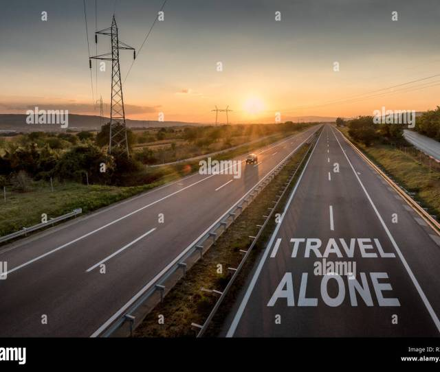 Beautiful Countryside Motorway With A Single Car At Sunset With Motivational Message I Travel Alone