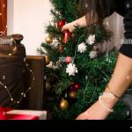 Woman Preparing Living Room For Christmas Evening