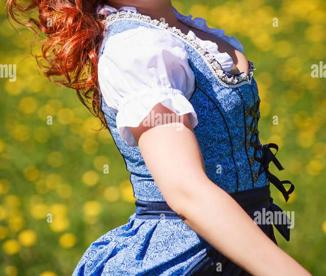 Beautiful Redhead Woman With Overweight In Dirndl Running Laughing Over A Flower Meadow
