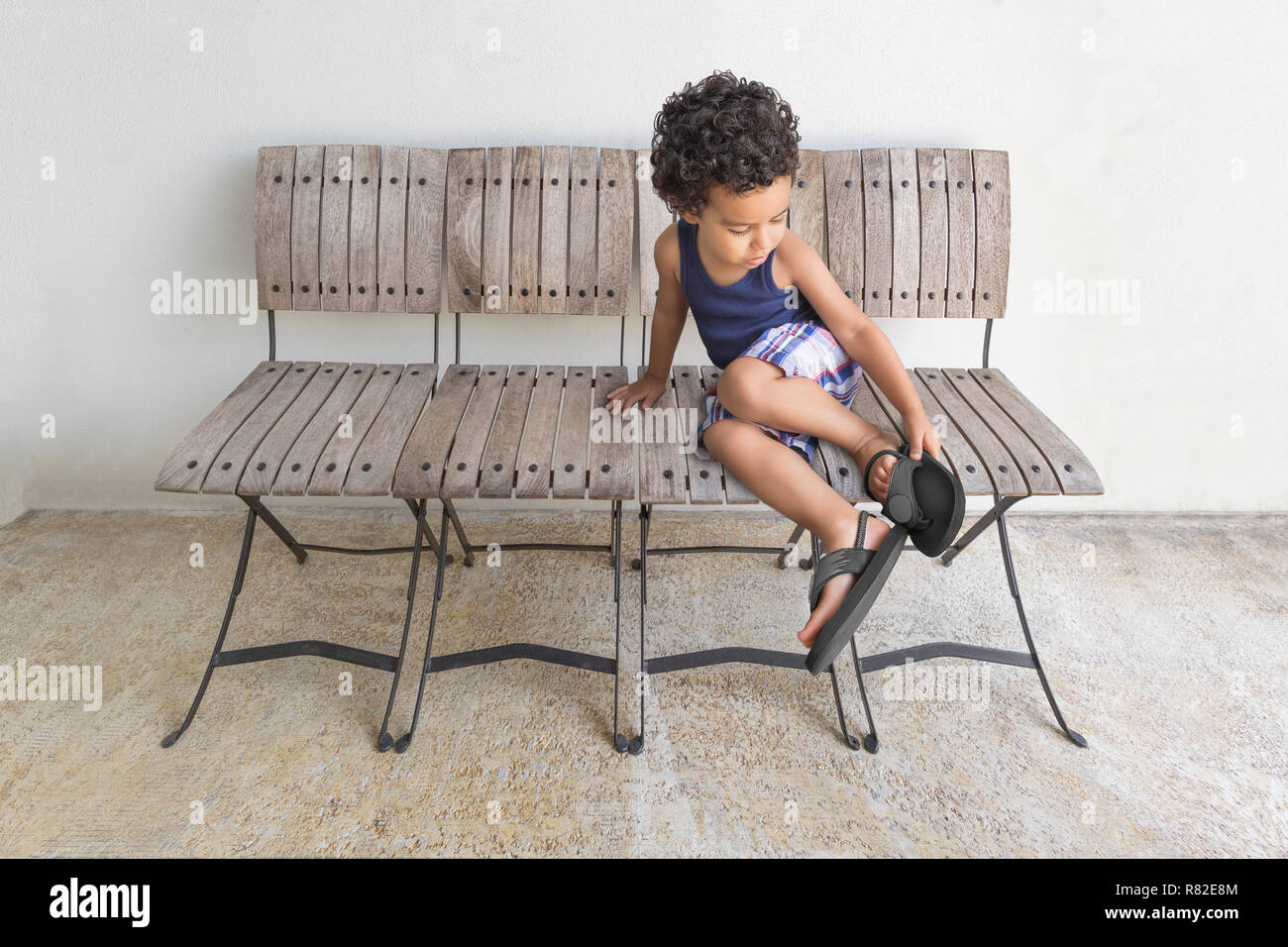 little boy chairs leather living room a determined puts on his shoes toddler sits row of four in the front porch putting own sandals to go out and play