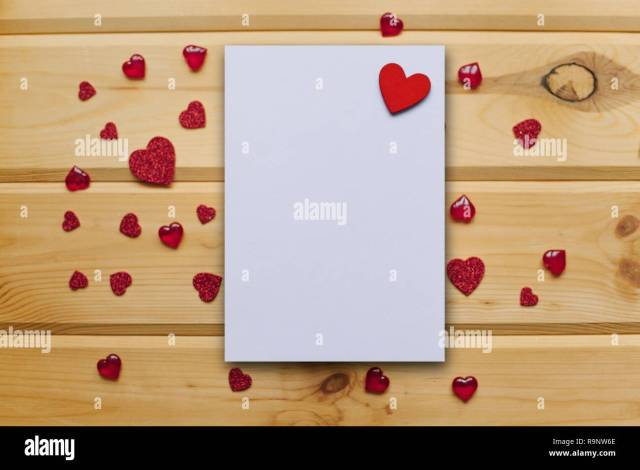 Blank sheet with red heart for text or write on a wooden surface