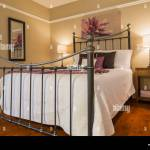 Queen Size Bed With White Bedspread And Antique Wrought Iron Headboard And Footboard In Guest Bedroom Inside A Contemporary Country House Stock Photo Alamy