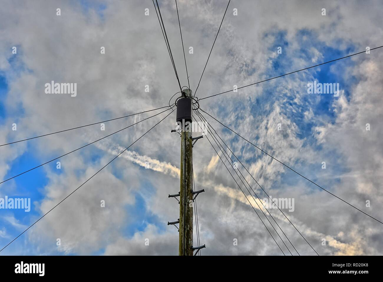 hight resolution of traditional telegraph pole with junction box and wires radiating across a partially cloudy sky with an