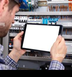 technician holding digital tablet with blank screen in front of fuse box stock image [ 1300 x 956 Pixel ]