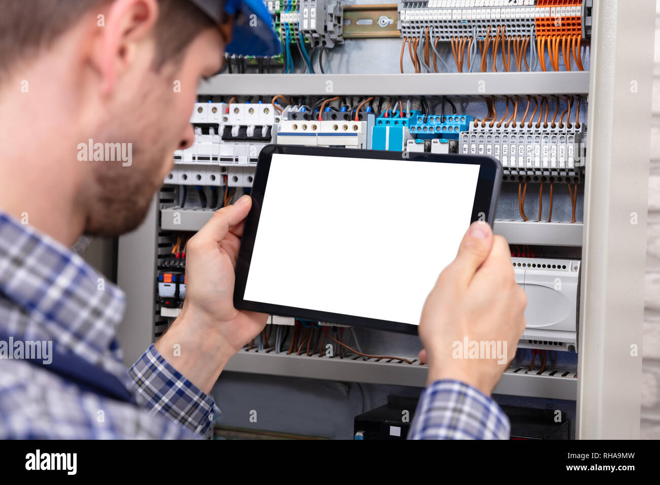 hight resolution of technician holding digital tablet with blank screen in front of fuse box stock image