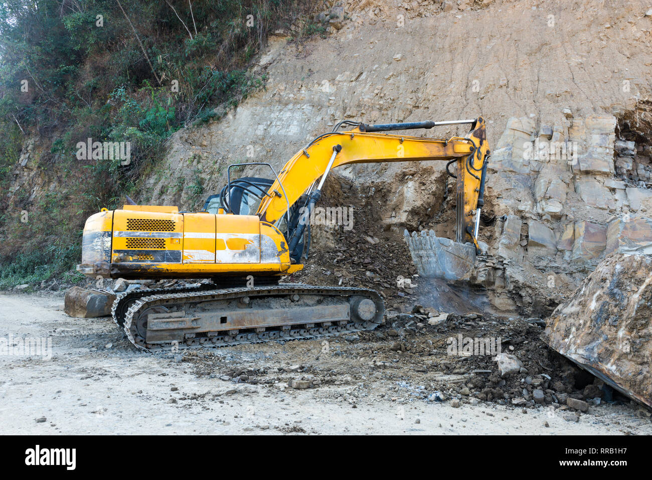 hight resolution of an excavator digs and collects soil and stone for a road widening project