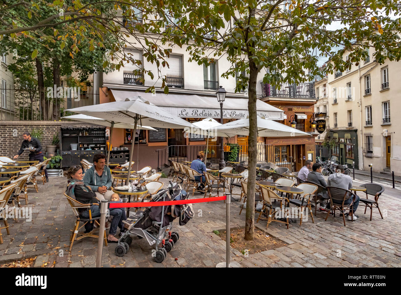 https www alamy com a couple with a baby relaxing at a table outside restaurant le relais de la butte whilst a waiter takes an order a restaurant in montmartre paris image239024373 html