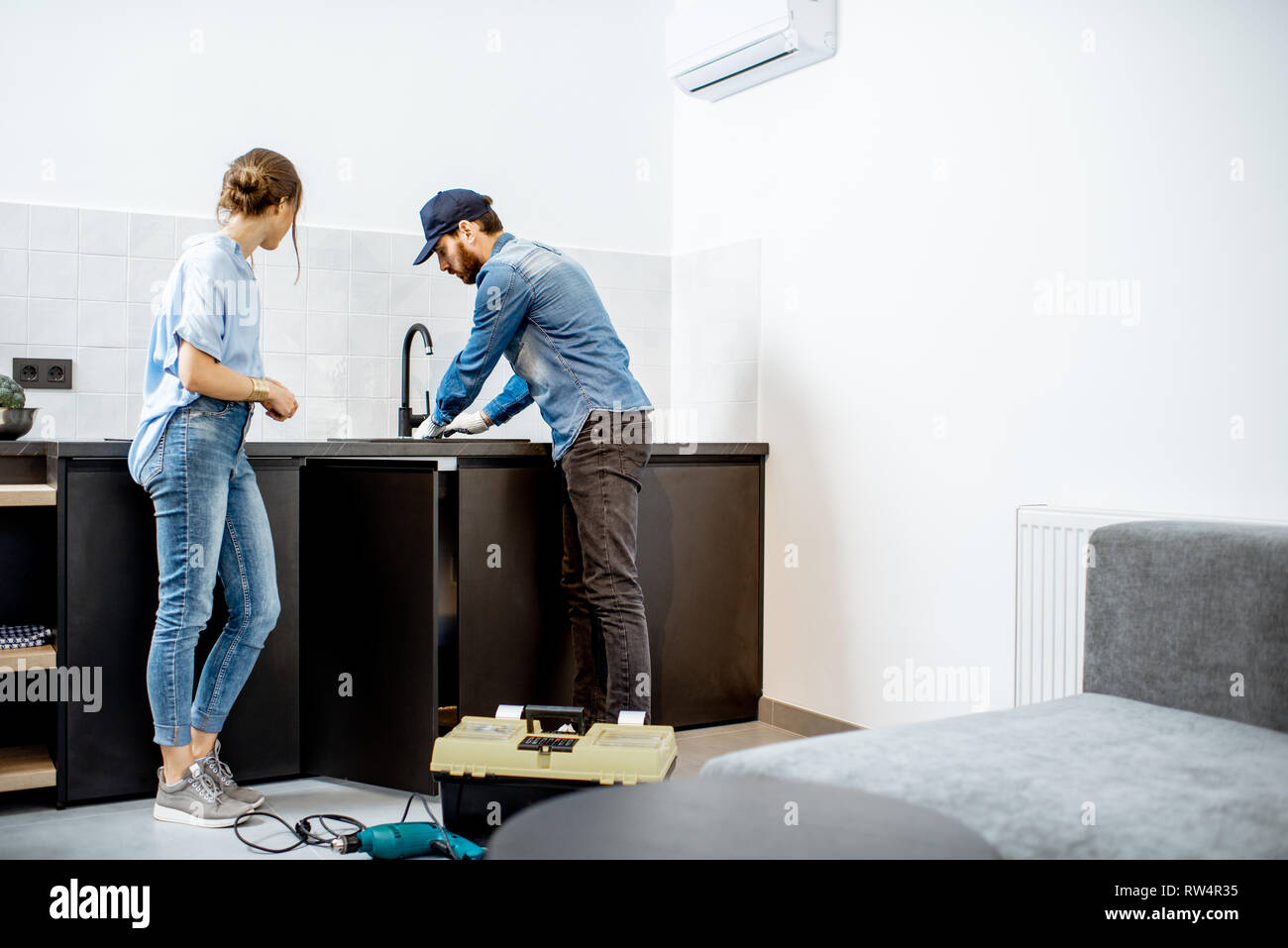 https www alamy com plumber or handyman repairing kitchen faucet standing with young woman in the apartment home repair service concept image239207113 html