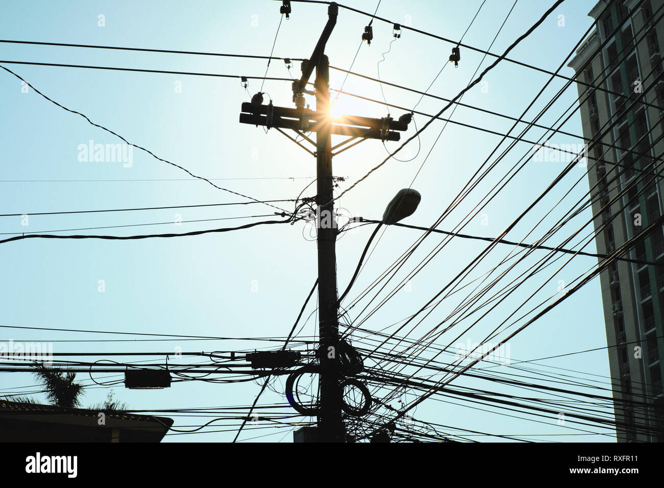 hight resolution of low angle view of concrete post for street lamp and electric wires at dusk thick network of cables in silhouette hanging on a pole in panama city co